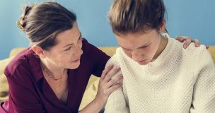 A teenager being comforted by a family friend after a traumatic grief and loss
